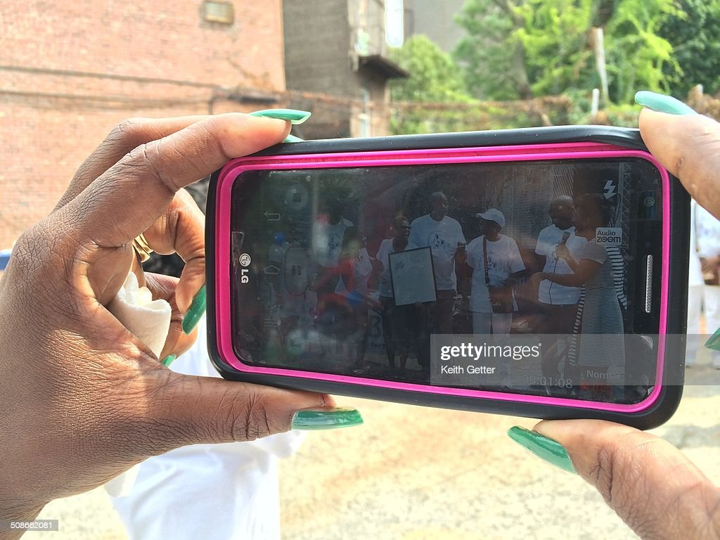 Stretching Fingers from Two Hands to Capture Image on a Phablet at a Community Event in Fort Greene, Brooklyn, NYC