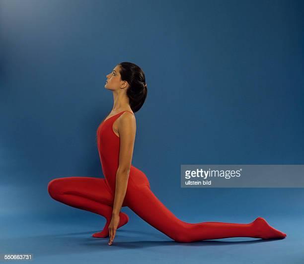 Stretching Fuesse Beine Wirbelsäule junges Mädchen roter Gymnastikanzug dunkelblonde Haare