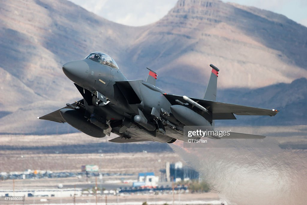 F-15E Strike Eagle flying past mountains