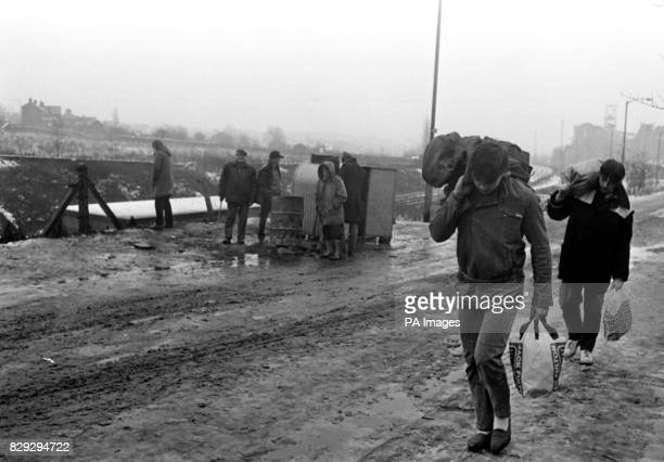 Strike pickets huddled around a brazier see miners who have returned to work on their way home with coal after working their shift at Kiveton park...