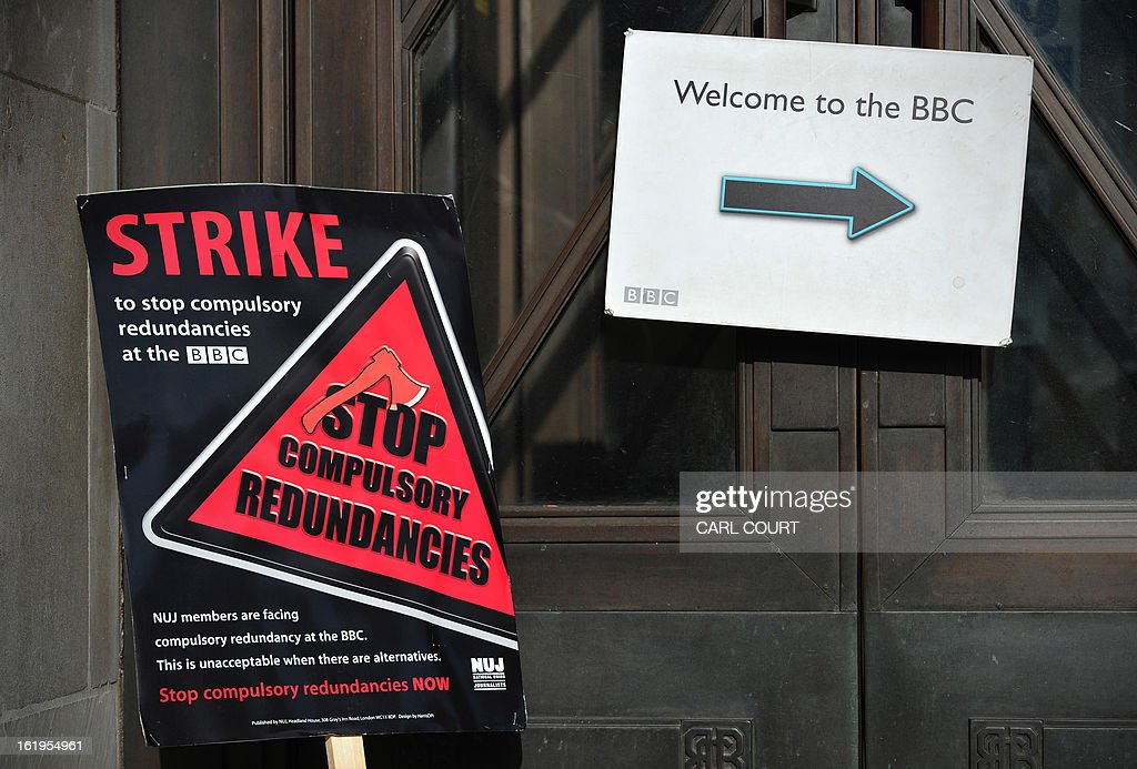 A strike placard is pictured next to a sign outside Broadcasting House in central London on February 18, 2013, as BBC staff man picket lines during a strike over compulsory redundancies. Today, February 18, 2013, BBC journalists began a 24-hour strike in protest at compulsory redundancies, causing possible disruption to the broadcaster's television and radio output. Members of the National Union of Journalists (NUJ) walked out at midnight (local time and GMT) at the end of Sunday's programming, over job cuts which are expected to affect BBC Scotland, Five Live, the Asian Network and the World Service. AFP PHOTO / CARL COURT
