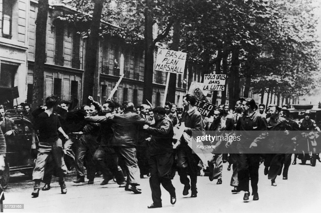 Strikers clash with police in the Place d'Augustin, Paris during a march to protest against the soaring cost of living in post-war France, 15th September 1948. One demonstrator carries a placard reading 'A Bas Le Plan Marshall' ('Down With The Marshall Plan').