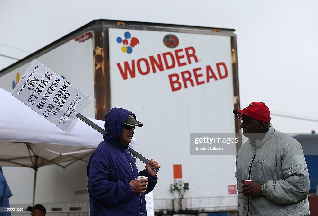 Striking bakery workers stand near a truck outside of the Interstate Bakeries facility on November 16, 2012 in Oakland, California. Hostess Brands, the maker of Twinkies, Ding Dongs and Wonder Bread, announced plans to liquidate its assets and lay off nearly 18,500 employees due to a workers strike brought on by an imposed contract that would cut workers' wages by 8 percent.
