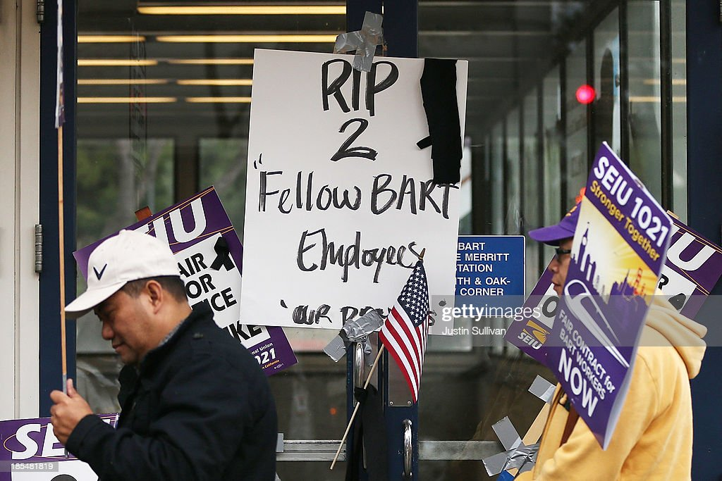 Striking Bay Area Rapid Transit (BART) workers walk in front of a sign honoring two BART workers who were struck and killed by a BART train over the weekend while servicing tracks near the Walnut Creek station on October 21, 2013 in Oakland, California. BART workers continue to strike after contract negotiations between BART management and the transit agency's two largest unions fell apart last week. Management and unions agreed on the financial specifics of the contract but differed on workplace safety rules. An estimated 400,000 commuters ride BART each day.