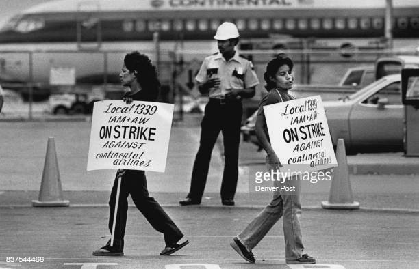 Striking Continental workers Judy Postrollo amd Rosie Montoya walk a picket line under the gaze of a security guard at the continental terminal...