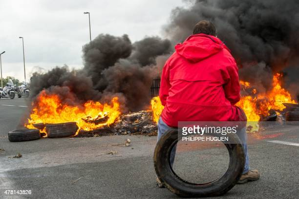 A striking employee of the French company My Ferry Link a crosschannel ferry service sits on a tyre in front of tyres set on fire as he takes part in...