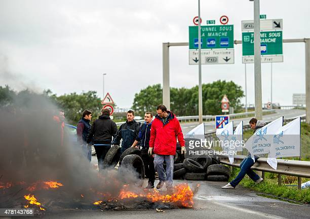 Striking employees of the French company My Ferry Link a crosschannel ferry service stand in front of tyres set on fire as they block the access to...