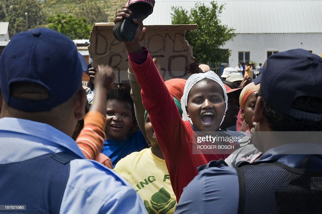 A striking farm worker holds a shoe up in the air as she protests with others in front of South African police on December 4, 2012 in Franschoek, 70Km north of Cape Town, to demand that their 70 rand (7 euros) wages be increased to 150 rand (15 euros). Farm workers in South Africa's picturesque winelands resumed strike action on December 4 - following strikes that turned violent in November - with tension enveloping the Western Cape region but few signs of a repeat of deadly violence.