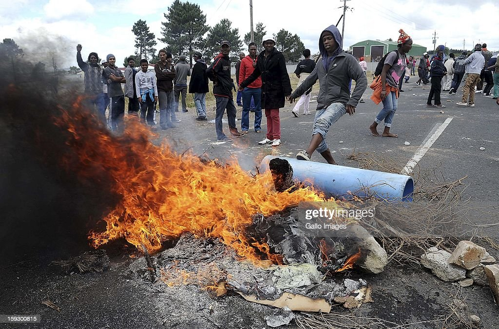 Striking farm workers set fire in protest at the N2 on January 10, 2013 in Grabouw, South Aifrca. Striking farm workers have blocked the highway as they continue striking.