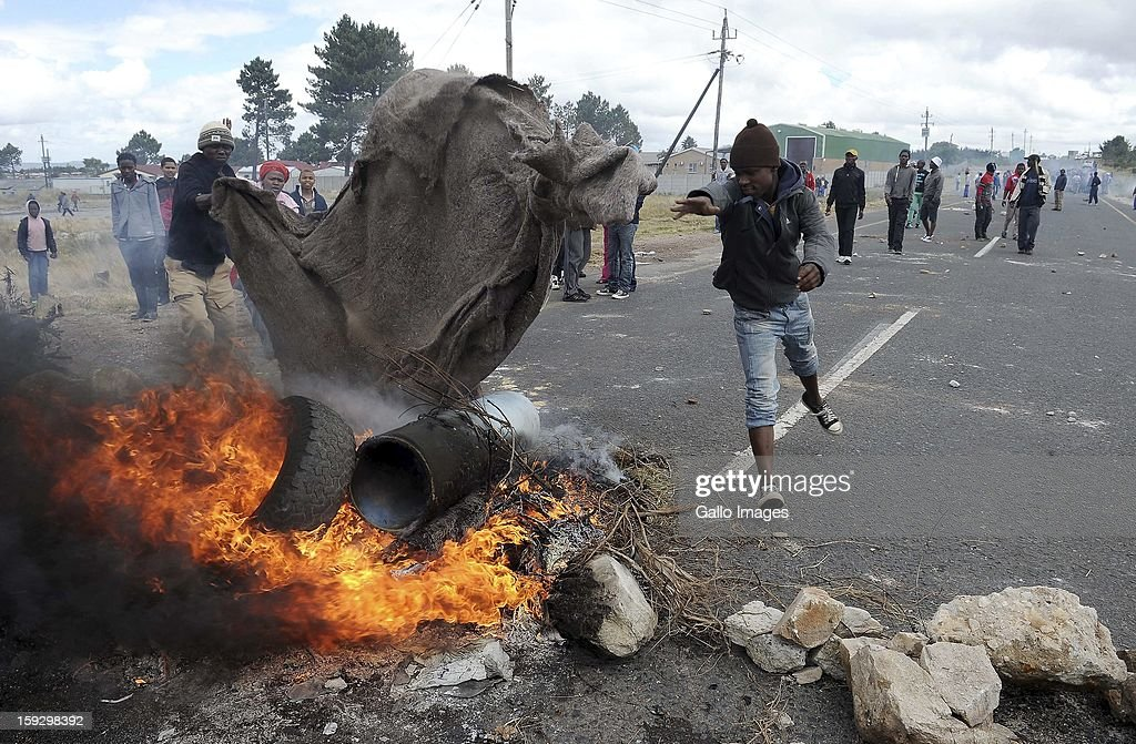 Striking farm workers set fire to tires on the N2 highway on January 10, 2013 in Grabouw, South Aifrca. Striking farm workers have blocked the highway as they continue striking.