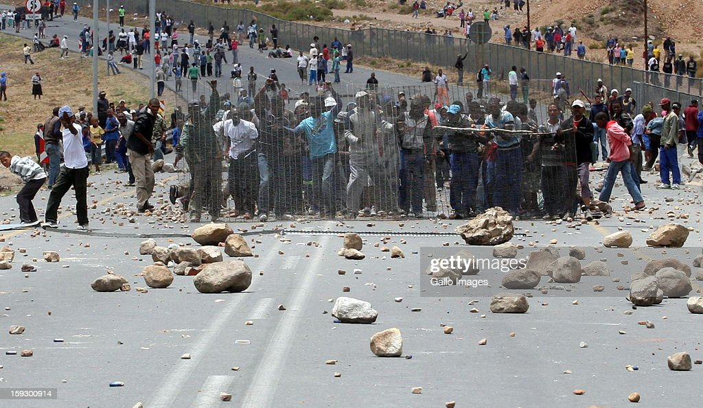 Striking Farm workers stand behind fencing as Police fight to hold them off from making barricades to block off the N2 on January 10, 2013 in Grabouw, South Africa. Seasonal farm workers are striking over wage disputes.