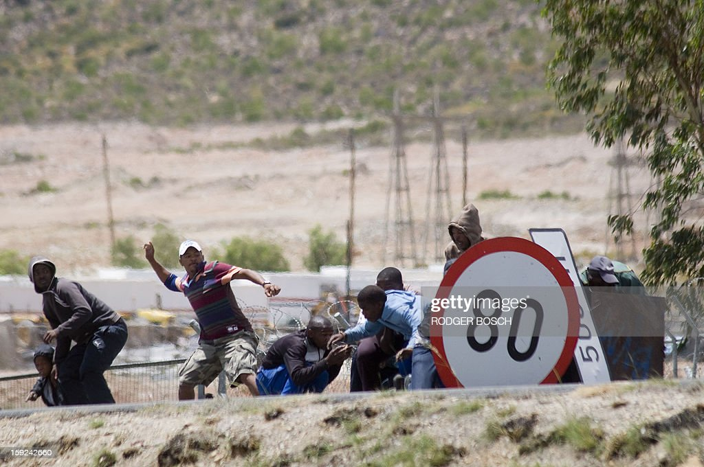Striking farmworkers and other protestors throw stones, while hiding behind broken road signs during violent clashes with members of the South African Police Services(not visible), on January 10, 2013 in de Doorns, a small farming town about 140Km North of Cape Town, South Africa. The farm workers have said that they they will not return to work on the fruit growing region's farms until they receive a daily wage of at least R150($17) per day, which is about double what they currently earn. AFP / RODGER BOSCH