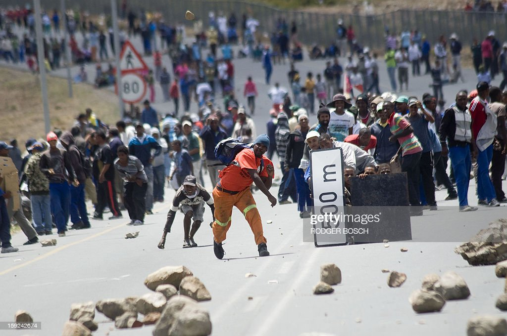 Striking farmworkers and other protestors throw stones, while hiding behind broken road signs during violent clashes with members of the South African Police Services(not visible), on January 10, 2013 in de Doorns, a small farming town about 140Km North of Cape Town, South Africa. The farm workers have said that they they will not return to work on the fruit growing region's farms until they receive a daily wage of at least R150($17) per day, which is about double what they currently earn. AFP PHOTO / RODGER BOSCH