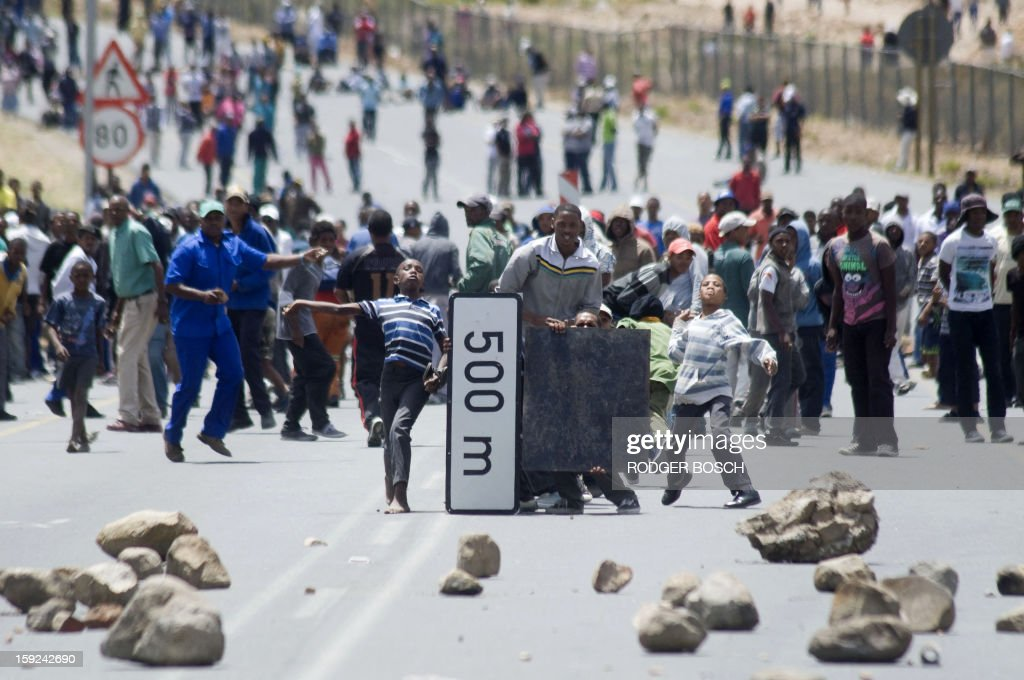 Striking farmworkers and other protestors throw stones, while hiding behind broken road signs during violent clashes with members of the South African Police Services(not visible), on January 10, 2013 in de Doorns, a small farming town about 140Km North of Cape Town, South Africa. The farm workers have said that they they will not return to work on the fruit growing region's farms until they receive a daily wage of at least R150($17) per day, which is about double what they currently earn.