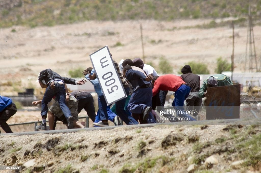 Striking farmworkers try to hide from police behind broken road signs during violent clashes, on January 10, 2013 in de Doorns, a small farming town about 140Km North of Cape Town, South Africa. The farm workers have said that they they will not return to work on the fruit growing region's farms until they receive a daily wage of at least R150($17) per day, which is about double what they currently earn.