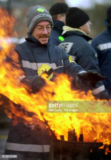 A striking fireman warms his hands over a brazier outside the Maryhill fire station in Glasgow The strike will last for 48 hours forcing troops to...