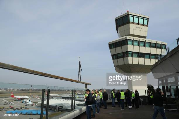 Striking ground personnel workers stand on a terrace under the control tower at Tegel Airport on March 13 2017 in Berlin Germany The strike is...
