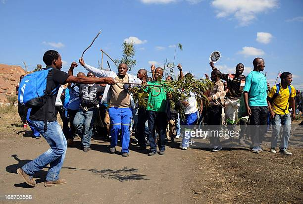 Striking Lonmin mine workers dance and sing while starting to gather next to a hill called Wonderkop on May 14 2013 in Marikana where 34 people were...