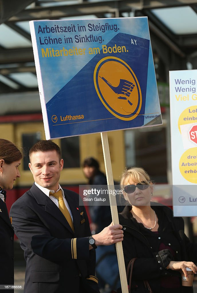 Striking Lufthansa employees gather at Tegel Airport under a protest sign during a nationwide strike by Lufthansa ground, service and maintenance personnel on April 22, 2013 in Berlin, Germany. Workers are demanding pay raises and job guarantees and today's strike has forced Lufthansa to cancel approximately 1700 flights.