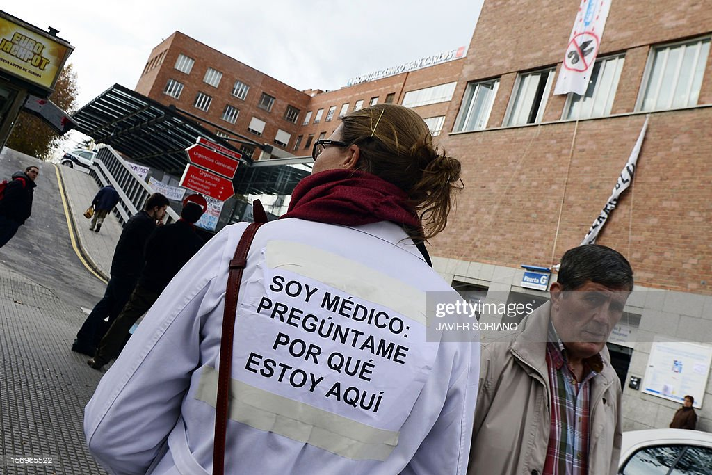 A striking medical worker walks outside the Hospital Clinico San Carlos in Madrid on November 26, 2012. Spanish doctors, nurses and hospital staff denounce budget cuts and privatisations. The health sector has been hard hit by the austerity policies implemented by the rightwing government of Mariano Rajoy, which is trying to cut the public deficit in the eurozone's fourth largest economy. The placard reads: 'I am a doctor: Ask me why I am here' AFP PHOTO / JAVIER SORIANO