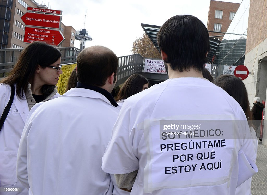 Striking medical workers walk outside the Hospital Clinico San Carlos in Madrid on November 26, 2012. Spanish doctors, nurses and hospital staff denounce budget cuts and privatisations. The health sector has been hard hit by the austerity policies implemented by the rightwing government of Mariano Rajoy, which is trying to cut the public deficit in the eurozone's fourth largest economy. The placard reads: 'I am a doctor: Ask me why I am here'