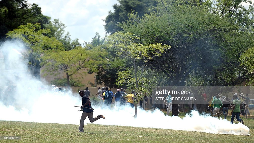 Striking miners run away as South African police officers fire rubber bullets, stun grenades and tear gas to disperse miners who were trying to prevent a rally organised by the Congress of South African Trade Unions (Cosatu) in Rustenburg, northwest of Johannesburg on October 27, 2012. Bullet casings littered the ground and a helicopter circled above, with police sirens howling, as the protesters were chased into the area surrounding the stadium. The clashes came a day after the National Union of Mineworkers (NUM) announced that it had reached a deal with the world's number one platinum producer Amplats to rehire 12,000 workers who were fired for a wildcat strike. Striking workers are disagree with the deal, which would signal a further winding down of a wave of wildcat strikes that have rocked platinum and gold mines since August.