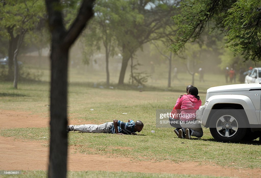 Striking miners shelter themselves as they run away while South African police officers fire rubber bullets, stun grenades and tear gas to disperse miners who were trying to prevent a rally organised by the Congress of South African Trade Unions (Cosatu) in Rustenburg, northwest of Johannesburg on October 27, 2012. Bullet casings littered the ground and a helicopter circled above, with police sirens howling, as the protesters were chased into the area surrounding the stadium. The clashes came a day after the National Union of Mineworkers (NUM) announced that it had reached a deal with the world's number one platinum producer Amplats to rehire 12,000 workers who were fired for a wildcat strike. Striking workers are disagree with the deal, which would signal a further winding down of a wave of wildcat strikes that have rocked platinum and gold mines since August. AFP PHOTO / STEPHANE DE SAKUTIN