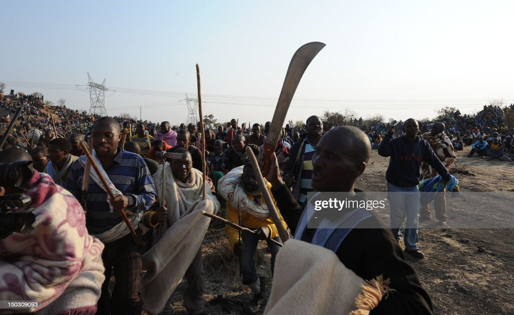 Striking mineworkers armed with machetes are monitered by a large number of police as they stage a sitin on a hill near the mine in Rustenburg 100...