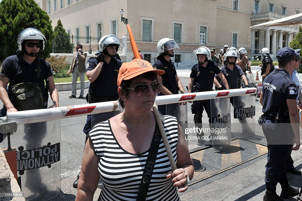 A striking municipal worker stands on July 9, 2013 in front of police forces protecting the Greek Parliament in Athens. Greek municipal workers went on strike for the second consecutive day on July 9, protesting against job cuts enacted by the government in return for promised EU-IMF rescue loans.