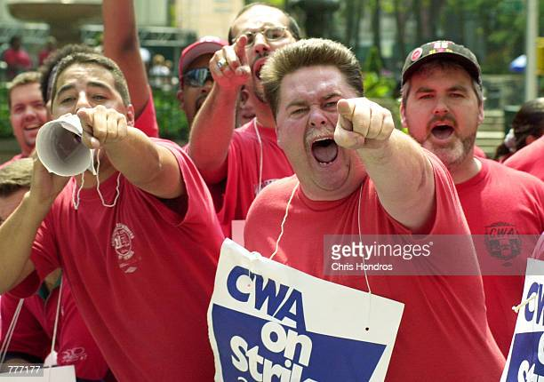 Striking telephone workers represented by the Communications Workers of America scream at workers not participating in their strike in front of...