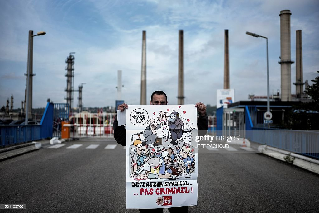 A striking worker holds a poster reading 'Union defender .. not criminal !' as he poses in front of the Total refinery of Feyzin, on May 25, 2016 to protest against the government's planned labour law reforms. France has been using strategic fuel reserves for two days in the face of widespread blockades of oil depots by union activists, the head of the oil industry federation said on May 25, 2016. PACHOUD