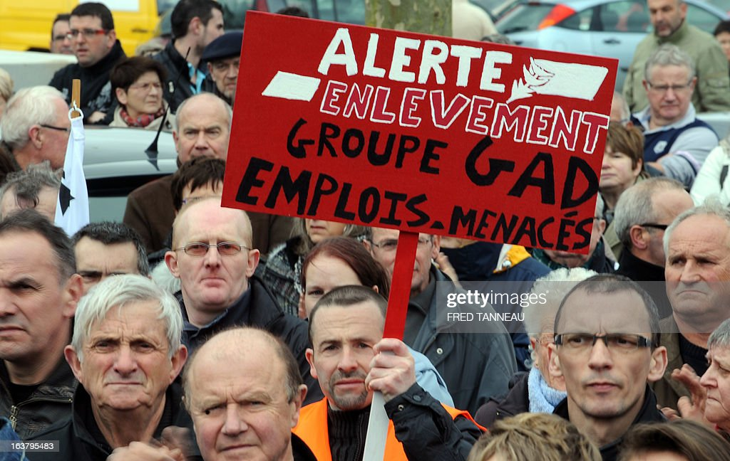A striking worker of the GAD SAS Lampaul slaughterhouse holds a placards reading 'Kidnapping alert, GAD company: jobs at risk' as he takes part in a demonstration in Landivisiau, western France, on March 16, 2013, against the closure of their company placed under judicial receivership in February 2013.