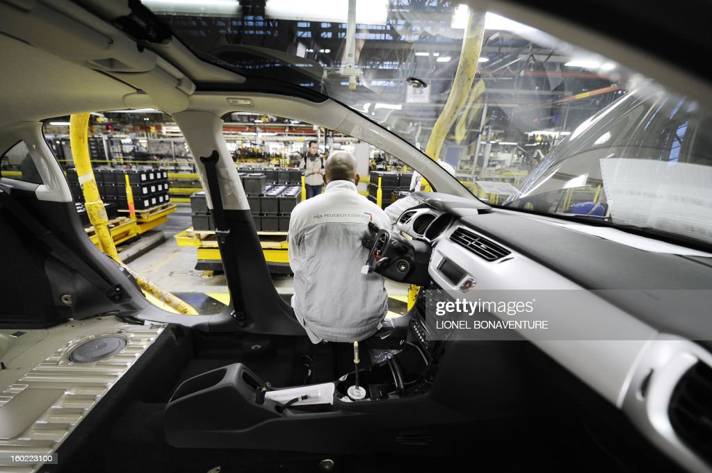 A striking worker of the PSA Peugeot Citroen carmaker plant of Aulnay-sous-Bois, a Paris' suburb, sits in a car being assembled, on January 28, 2013 at the plant, during a general assembly. The striking workers occupy the factory to protest against plans to sell the plant and lay off thousands of employees. AFP PHOTO LIONEL BONAVENTURE