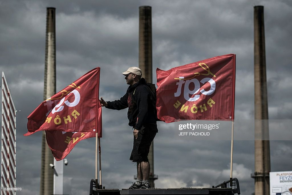 A striking worker stands next to French CGT union flags in front of the Total oil refinery of Feyzin, near Lyon, central-eastern France, on May 24, 2016, during a strike at the plant to protest against government labour reforms. France's government stepped up efforts on May 24 to break blockades and strikes at refineries that are threatening to paralyse the country just three weeks ahead of the Euro 2016 football tournament. Six out of eight of the refineries in France have either stopped operating or have reduced output due to strikes and blockades. PACHOUD