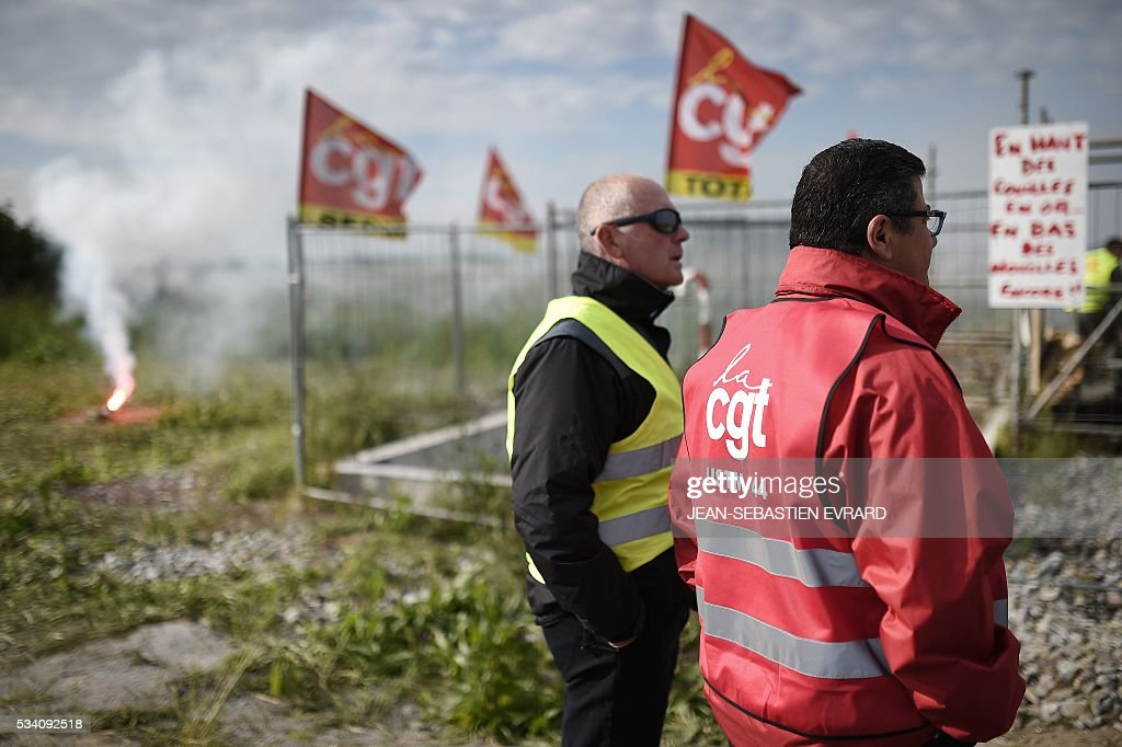Striking workers block the access to an oil depot near the Total refinery of Donges, western France, on May 25, 2016, to protest against the government's planned labour law reforms. France has been using strategic fuel reserves for two days in the face of widespread blockades of oil depots by union activists, the head of the oil industry federation said on May 25, 2016. / AFP / JEAN