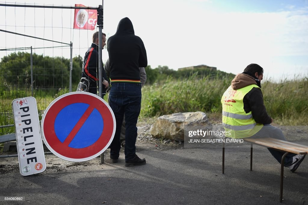 Striking workers block the access to an oil depot near the Total refinery of Donges, western France, on May 25, 2016 to protest against the government's planned labour law reforms. France has been using strategic fuel reserves for two days in the face of widespread blockades of oil depots by union activists, the head of the oil industry federation said on May 25, 2016. / AFP / JEAN