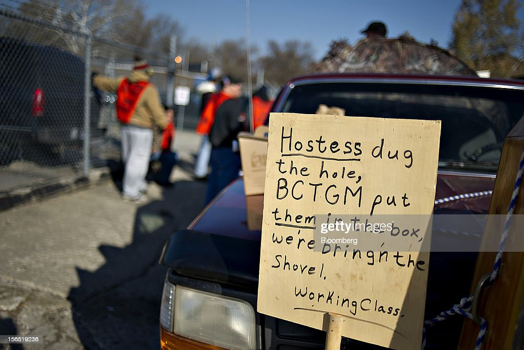 Striking workers display a sign while picketing outside a Hostess Brands Inc. bakery in Peoria, Illinois, U.S., on Friday, Nov. 16, 2012. Hostess Brands Inc., the bankrupt maker of Wonder bread and Twinkies, said it will fire more than 18,000 workers and liquidate after a nationwide strike by bakery workers crippled operations. Photographer: Daniel Acker/Bloomberg via Getty Images