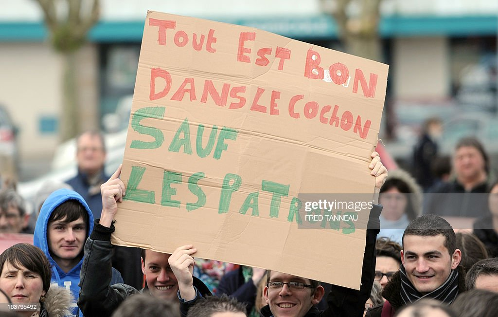 Striking workers of the GAD SAS Lampaul slaughterhouse holds a placards reading 'Everything is good in pig except the bosses' as they take part in a demonstration in Landivisiau, western France, on March 16, 2013, against the closure of their company placed under judicial receivership in February 2013.