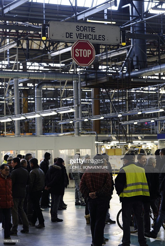Striking workers of the PSA Peugeot Citroen carmaker plant of Aulnay-sous-Bois, a Paris' suburb, take part in a general assembly, on January 28, 2013. The striking workers occupy the factory to protest against plans to sell the plant and lay off thousands of employees.