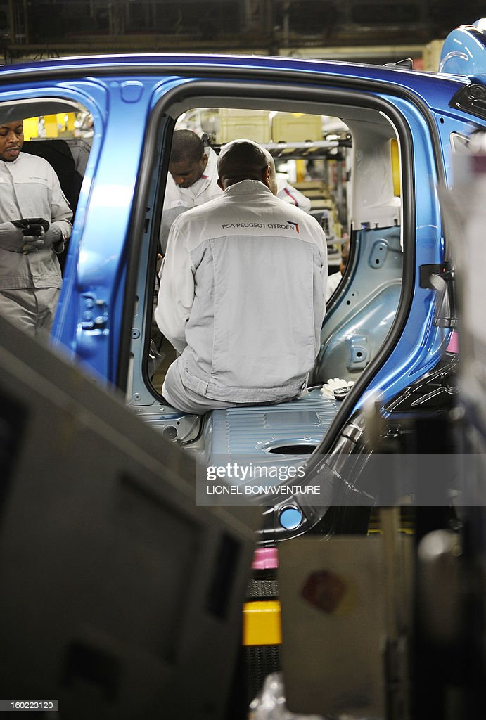 A striking workers of the PSA Peugeot Citroen carmaker plant of Aulnay-sous-Bois, a Paris' suburb, sits in a car being assembled, on January 28, 2013 at the plant, during a general assembly. The striking workers occupy the factory to protest against plans to sell the plant and lay off thousands of employees. AFP PHOTO LIONEL BONAVENTURE