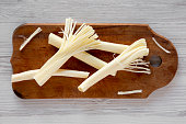 String cheese on rustic wooden board over white wooden background, top view. Healthy snack. Flat lay, overhead, from above.