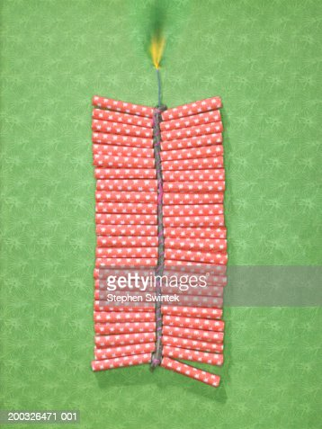 String of  firecrackers with lit fuse on green patterned paper