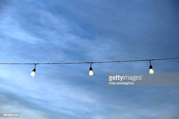 String of Lightbulbs Against a Cloudy Sky