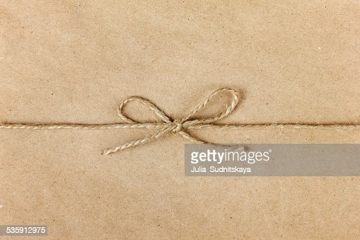 string or twine tied in bow on kraft paper background : Stock Photo