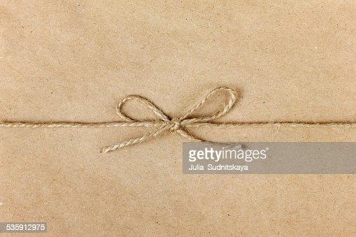 Cadeia ou cordéis presa em arco sobre fundo de papel kraft : Foto de stock