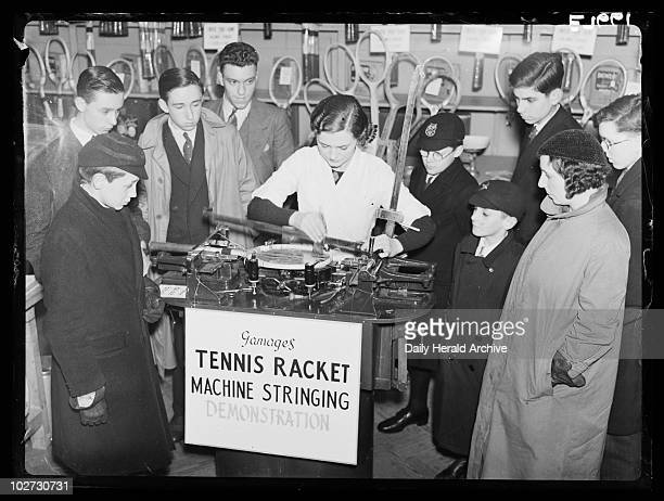 Stringing a tennis racket Gamages Oxford Street London 1936 A photograph of a woman demonstrating a machine for stringing tennis rackets at Gamages...