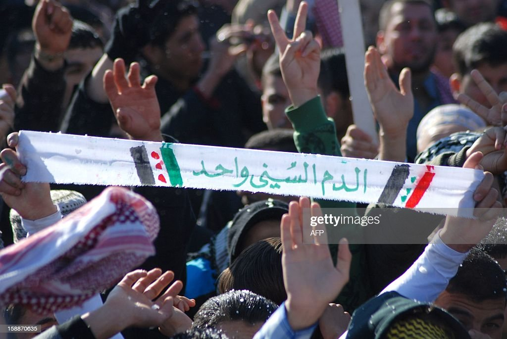 A strip of cloth with the words in Arabic that read, 'Sunni Muslim blood is one', is held up as Iraqis rally in the city of Samarra,on January 2, 2013, as Protesters in mostly Sunni areas of Iraq's west and north have alleged that the Shiite-led authorities use anti-terror legislation to target their minority community. Iraqi premier Nuri al-Maliki looked to head off protests in Sunni areas of the country with a prisoner release even as he threatened to use state resources to 'intervene' to end the rallies. AFP PHOTO/MAHMOUD AL-SAMARRAI