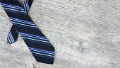 Striped blue and black tie over wooden background with copy space