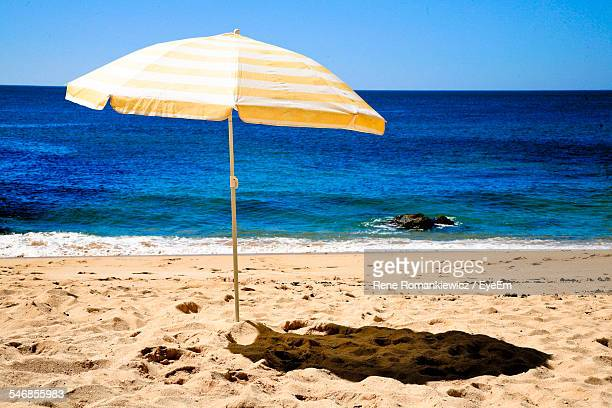 Striped Parasol On Beach Against Clear Sky