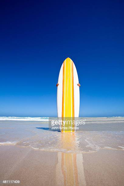Striped retro surf board on a beach. Australia